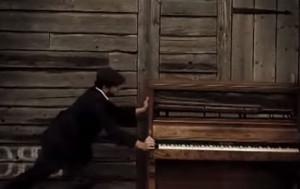 Человек толкает пианино